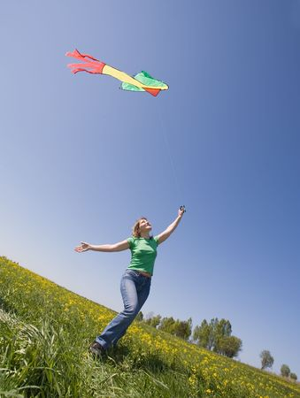 young woman flying kite on a green meadow