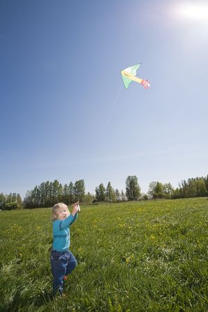young girl flying kite on a green meadow