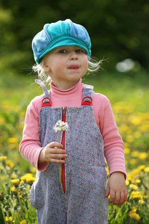 little girl in blue cap on a beautiful summer meadow photo