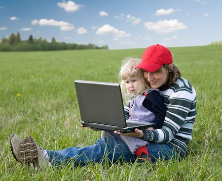 young mother and daughter sitting with laptop computer on green grass meadow Stock Photo - 3177665