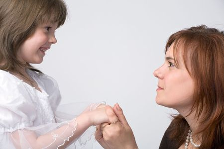 tenderly: faces in profile of mother and daughter looking at each other holding by hands on grey background Stock Photo