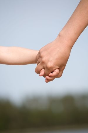 handclasp: mother and child holding hands closeup on sky background Stock Photo
