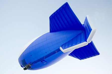 blimp: flying blimp on clear blue sky background