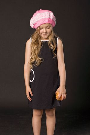insidious: sly little girl with yellow apple in hand on black background