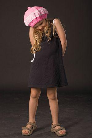 sly little girl posing in studio on black background photo