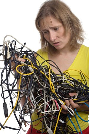muddle: sad woman with tangle of cables and wires in hands isolated on white