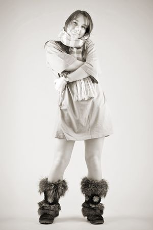 moccasins: smiling young woman in long t-shirt, fur moccasins and striped muffler standing on grey background