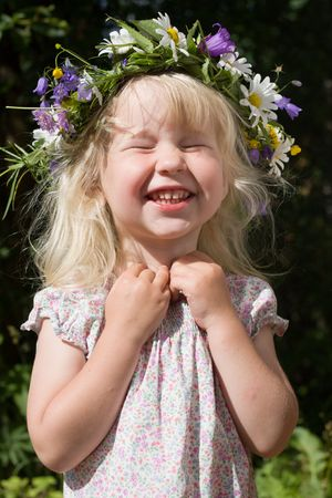 laughing little girl in flowers wreath on green meadow Stock Photo