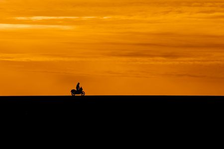 black silhouette of biker on orange sunset sky background photo