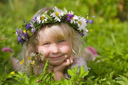 happy little girl in flowers wreath lying on green meadow
