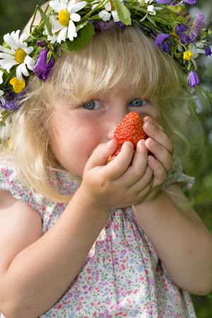 happy little girl in flowers wreath with strawberries in hands photo