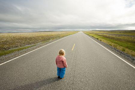 empezar: ni�o peque�o de pie en el comienzo de recta carretera que va a horizonte