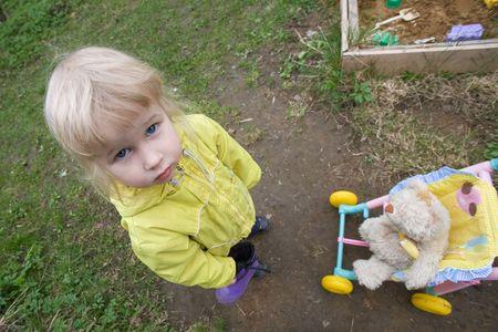 perambulator: top view of little girl near her perambulator with toy cat