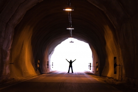 woman silhouette at the exit from dark tunnel photo