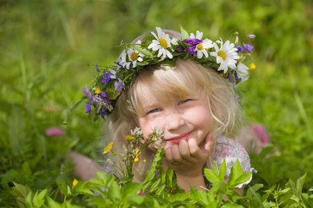 happy little girl in flowers wreath lying on green meadow photo
