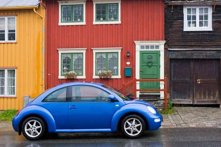 beautiful modern car on old style wooden colorful houses background of street in small town in Norway Stock Photo