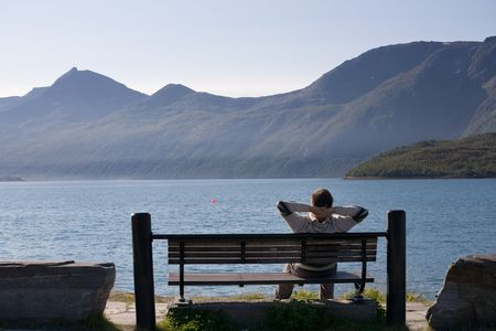 pacification: relaxed man sitting on the bank of lake Stock Photo