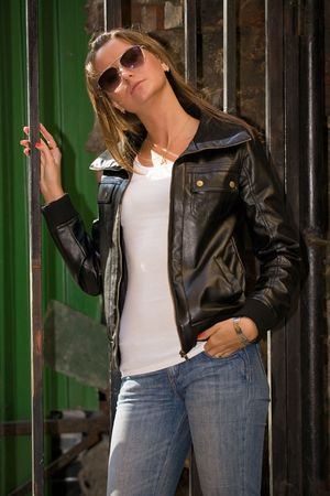 beautiful girl in jeans, leather jacket and sun glasses