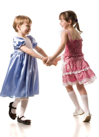two little dancing girl in beautiful dresses, isolated on white Stock Photo