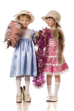 Two little girls with tinsel, feather and fur in mums shoes and in hats, isolated on white