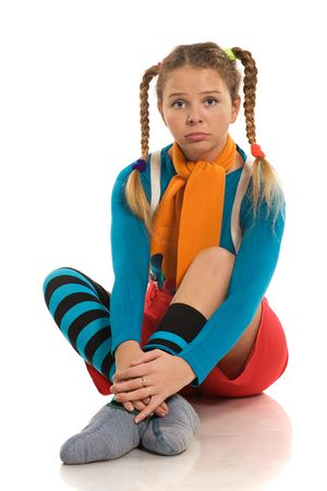beautiful sad girl in colour cheerful clothes sitting on the floor photo