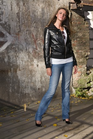 beautiful girl in jeans and a black leather jacket standing before stone wall Stock Photo - 3941637