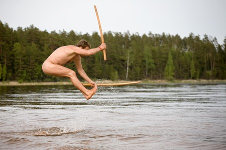 nude man with two wooden samurai swords jumps in water
