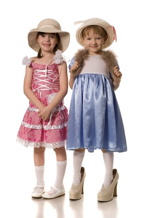 big shoes: two little girls in hats and mums shoes, isolated on white Stock Photo