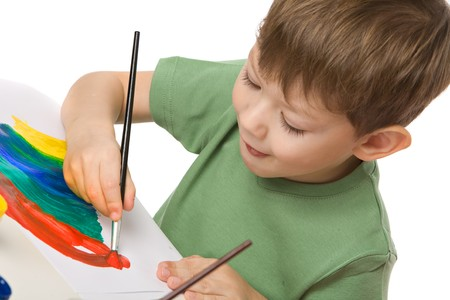 boy draws with paints on paper with tongue hanging out, isolated on white