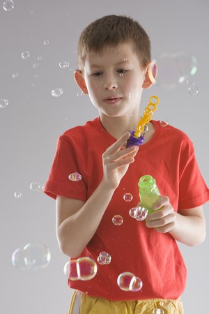 boy in a red T-shirt blows soap bubbles, on grey background photo