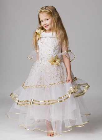 beautiful little girl in princess dress with long hair barefoot stand on grey background Stock Photo