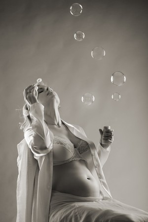 beautiful pregnant woman in underwear sit and blows bubbles, sepia toned Stock Photo - 4022811