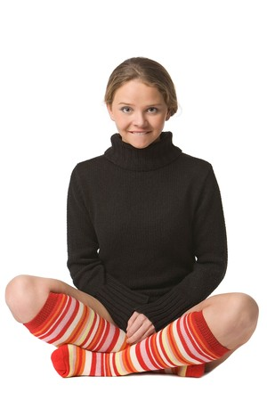 beautiful girl in sweater and long red-orange socks sits on floor crossed legs in funny yogi pose photo