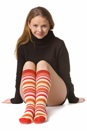 long socks: beautiful girl with long hair in sweater and long red-orange socks sits on the floor, isolated on white