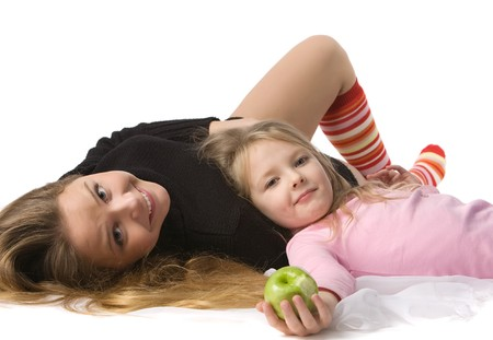 sweater girl: beautiful little daughter with apple in pink jacket lies on mums stomach, isolated on white