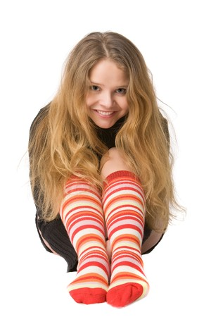 laughing girl with long hair in long brown sweater and red-orange long socks sitting on the floor, isolated on white Stock Photo - 4031261