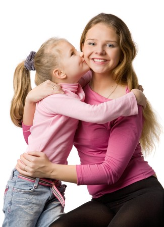 Mum and the daughter in pink clothes, daughter kisses mum, isolated on white photo