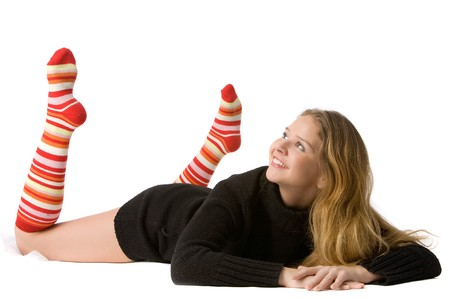 long socks: beautiful smiling girl in brown sweater and long red-orange socks lies on the floor and looks upward, isolated on white