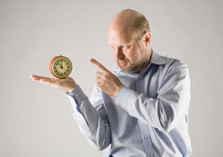 man shows at clock standing on his hand, isolated on grey photo
