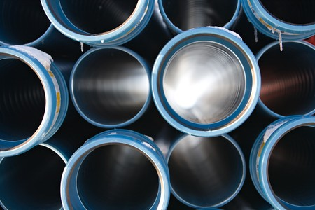 pvc: blue pipes stacked in construction site, pattern closeup Stock Photo