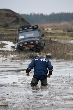 Russian rescuer stand in cold water near to  got stuck car