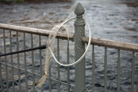 landing net hanging on grey iron  fencing over the water photo