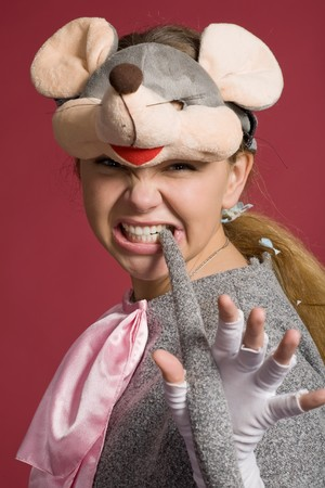 conspicuous: aggressive girl in  mouse suit holds  tail in  teeth on red background Stock Photo