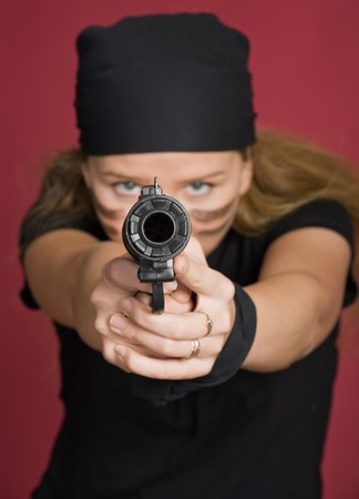 beautiful aggressive girl-pirate close-up directs a pistol on you on red background photo