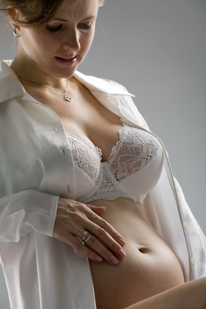 beautiful pregnant girl sits and stroke  stomach photo