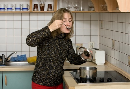 woman on kitchen tasting dinner from a spoon photo