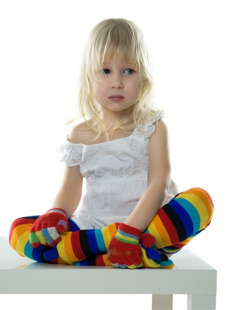 stools: little girl in  white dress, multi-coloured stockings and colour gloves sits on white chair