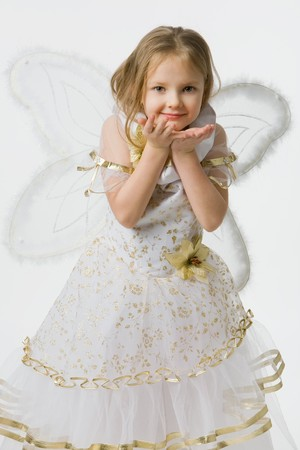 little girl in  beautiful dress with wings of the butterfly sends  air kiss, isolated on white