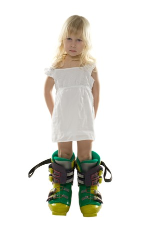 big foot: little girl in a white dress and big ski boots holds hands behind the back, isolated on white