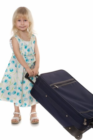 beautiful little girl a white-blue dress carries suitcase, isolated on white photo
